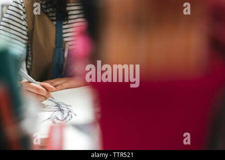 Midsection of female artisan drawing on book in workshop - Stock Photo
