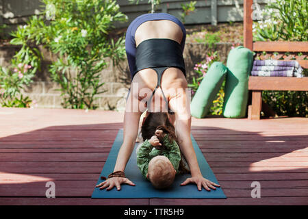 Woman exercising with baby on mat at backyard - Stock Photo