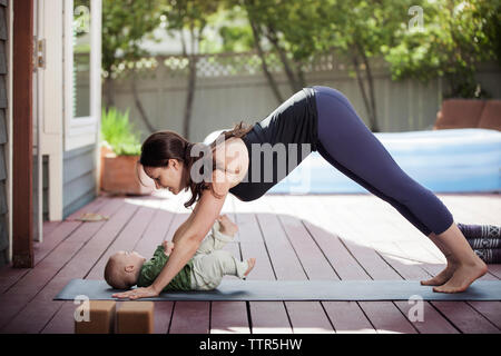 Side view of woman practicing downward facing dog position while looking at baby in backyard - Stock Photo