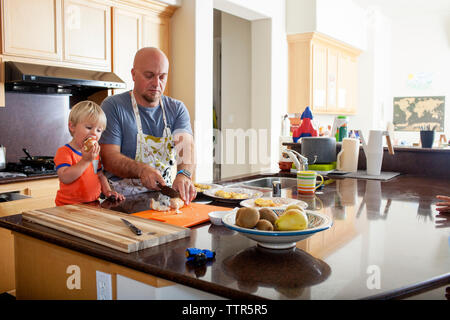 Boy eating apple while father chopping potatoes at kitchen counter - Stock Photo