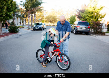 Father teaching son to ride bicycle on road - Stock Photo