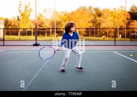 Boy playing tennis at court - Stock Photo