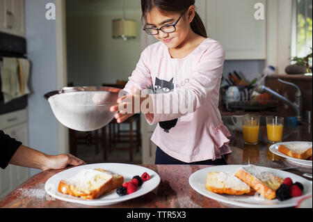 Girl sprinkling powdered sugar on bread with mother in kitchen - Stock Photo