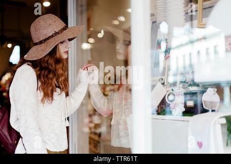 Woman wearing sun hat doing window shopping in city - Stock Photo