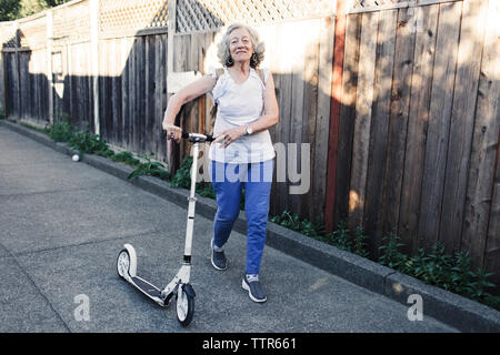 Portrait of confident senior woman walking with push scooter in yard - Stock Photo