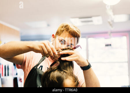 Hairdresser cutting customer's hair at barber shop - Stock Photo