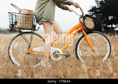 Low section of teenage girl riding bicycle amidst plants on field - Stock Photo