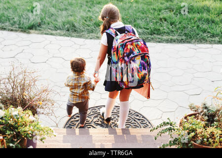 High angle view of sister wearing school uniform while holding brother's hand - Stock Photo