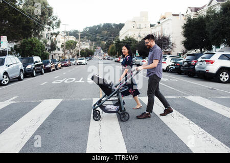 Parents with daughter in baby stroller walking on city street - Stock Photo