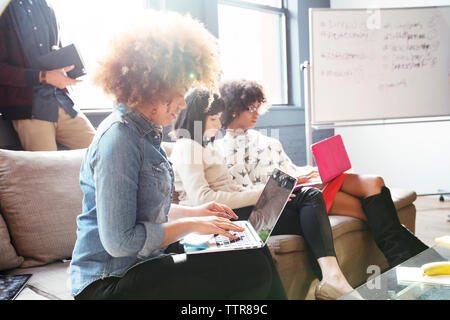 Businesswomen using laptop computer while sitting on sofa in office - Stock Photo