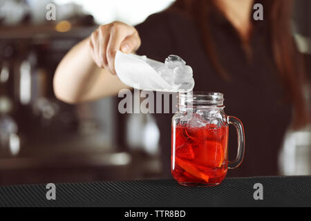 Woman hands adding ice into cocktail on bar counter - Stock Photo