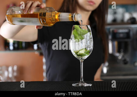 Woman hands making cocktail on bar counter - Stock Photo