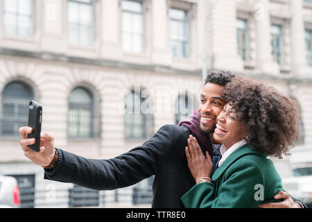 Business couple taking selfie while standing in city - Stock Photo