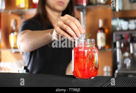 Woman hands putting straws into cocktail on bar counter - Stock Photo