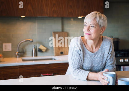 Thoughtful senior woman looking away while leaning on table - Stock Photo
