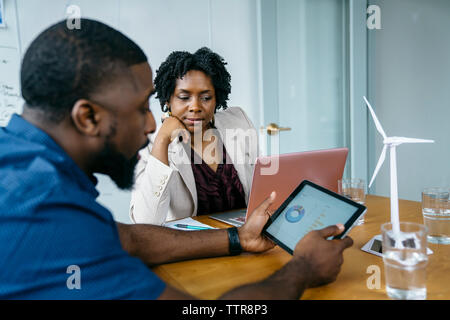 Businessman showing pie chart in digital tablet to female colleague - Stock Photo