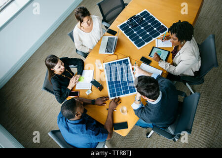 Overhead view of business people discussing over solar panel models during meeting - Stock Photo