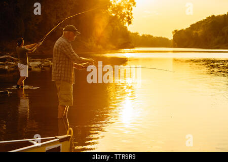 Friends fishing while standing in lake during sunset - Stock Photo