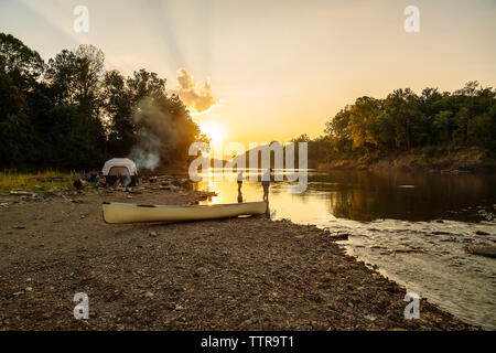 Young man sitting at campsite while friends fishing in lake against sky during sunset - Stock Photo