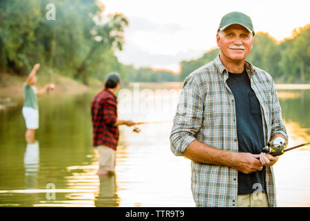 Portrait of smiling senior man fishing with friends in lake against sky - Stock Photo