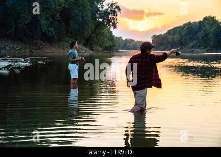 Male friends fishing while standing in lake during sunset - Stock Photo