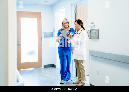 Female doctors discussing over tablet computer while standing in hospital corridor - Stock Photo