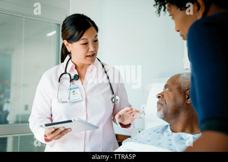 Doctor with tablet computer talking to senior patient lying by daughter in hospital ward - Stock Photo