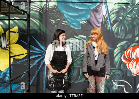 Female painters looking at each other while standing against mural on wall - Stock Photo
