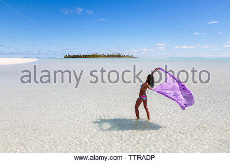 Woman holding sarong while standing in Aitutaki lagoon against blue sky - Stock Photo