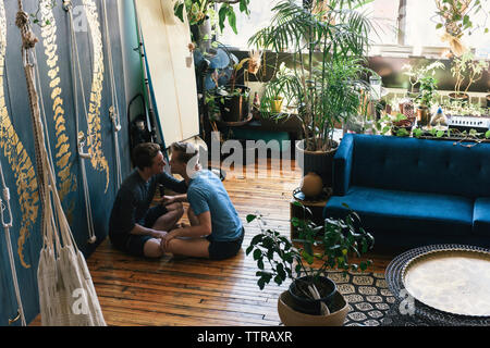 Side view of gay couple kissing while sitting on hardwood floor at loft apartment - Stock Photo