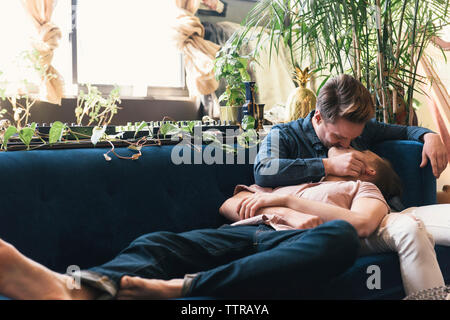 Gay couple kissing on sofa against potted plants at home - Stock Photo