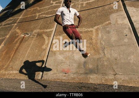 Low angle view of happy male dancer with hands in pockets jumping against old wall during sunny day - Stock Photo