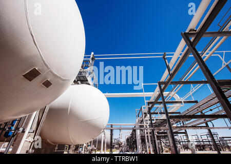 Natural gas tanks in oil refinery against clear sky - Stock Photo