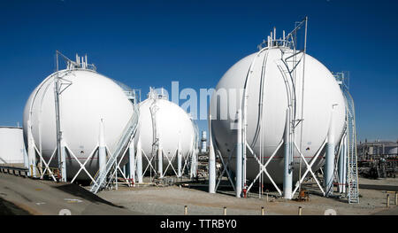 Refinery storage tanks against clear blue sky on sunny day - Stock Photo