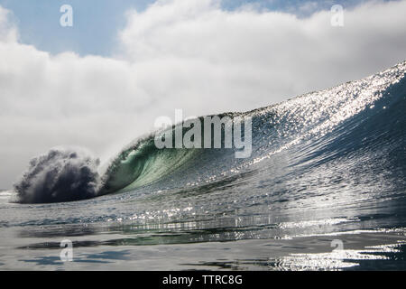 Scenic view of waves splashing against cloudy sky - Stock Photo