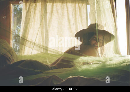 Portrait of shirtless woman lying on bed with mosquito netting in room - Stock Photo