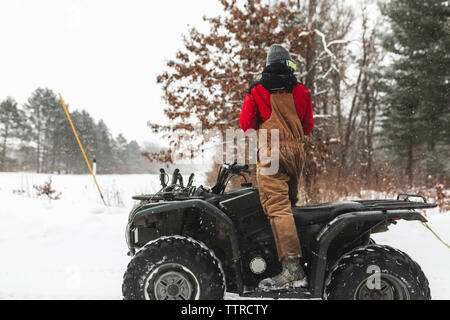 Rear view of teenage boy standing on quad bike in forest during winter - Stock Photo