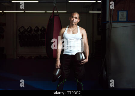 Portrait of sportsman holding boxing gloves standing in gym - Stock Photo