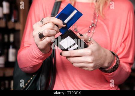 Midsection of female customer swiping credit card at wine shop - Stock Photo