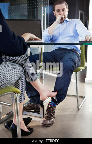Low section of businesswoman playing footsie with male colleague at conference table - Stock Photo