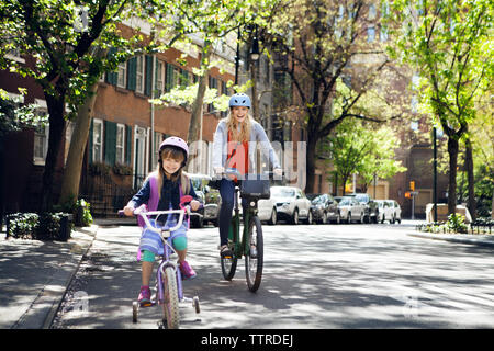 Portrait of cheerful mother and daughter riding bicycles on street - Stock Photo