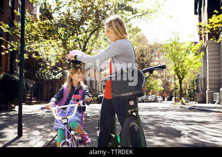 Side view of woman putting helmet on daughter riding bicycle on street - Stock Photo