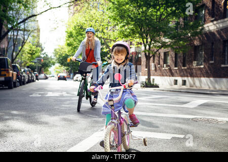 Portrait of happy mother and daughter riding bicycles on street - Stock Photo