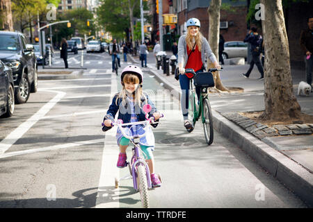 Portrait of mother and daughter riding bicycles on street - Stock Photo