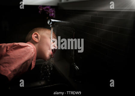 Side view of boy drinking water from faucet in kitchen at home - Stock Photo
