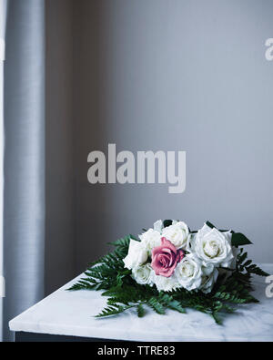 Rose bouquet on table against wall at home - Stock Photo