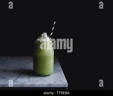 Close-up of matcha shake in bottle on marble counter against black background - Stock Photo