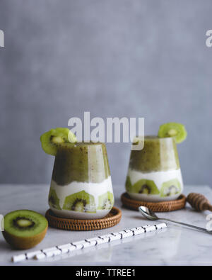 Close-up of kiwi smoothie served in drinking glasses on table - Stock Photo