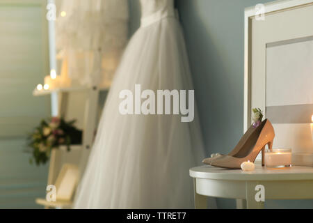 Shoes on table and wedding dress in room - Stock Photo