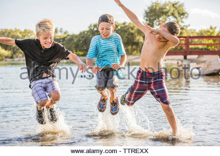 Happy friends jumping in lake - Stock Photo